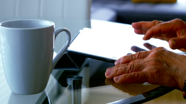 Senior woman using digital tablet in living room video