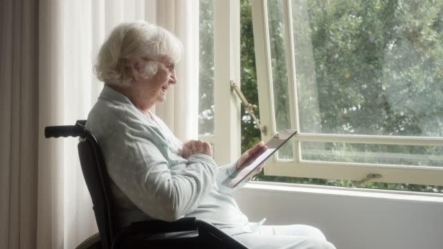 donna anziana che usa tablet digitale su sedia a rotelle - donne anziane video stock e b–roll