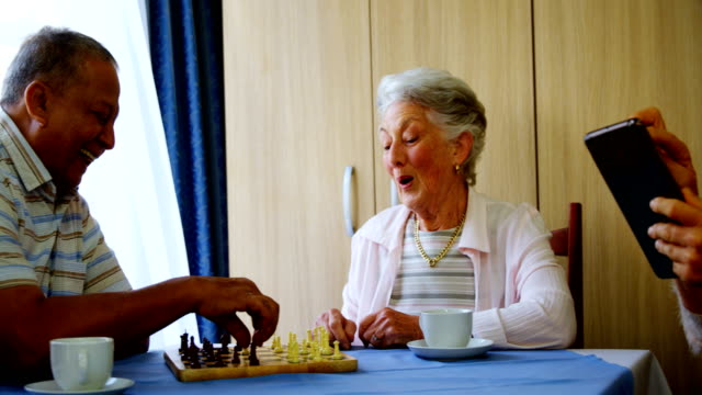 senior woman using digital tablet while her friends playing chess 4k - 60 69 anni video stock e b–roll