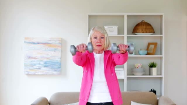 Senior woman using dumbbells at home video
