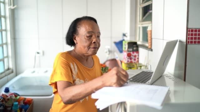 vidéos et rushes de femme aîné utilisant l'ordinateur portatif et écrivant quelques notes à la maison - recette