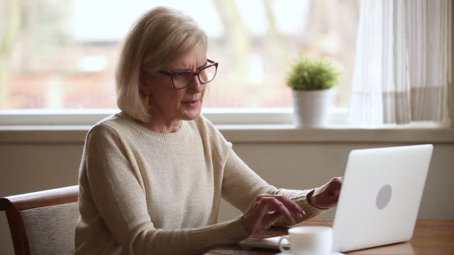 Senior woman using laptop feeling discomfort taking off glasses Senior woman using laptop feeling discomfort from dry irritated fatigued eyes taking off glasses, older mature businesswoman tired of computer worker suffering from blurry vision eyestrain problem exhaustion stock videos & royalty-free footage