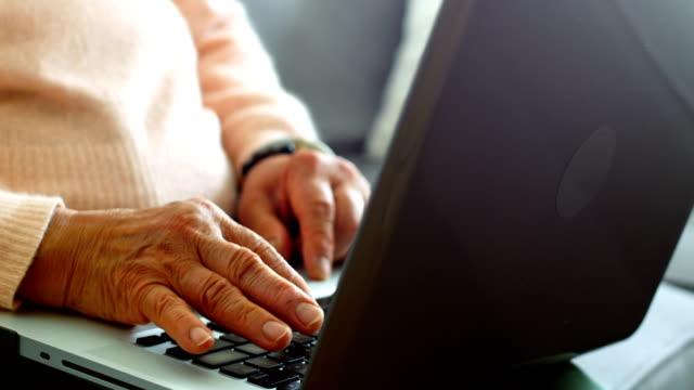 Senior woman using laptop in living room video