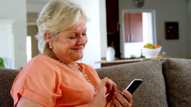 senior woman using mobile phone in living room 4k - 60 69 anni video stock e b–roll
