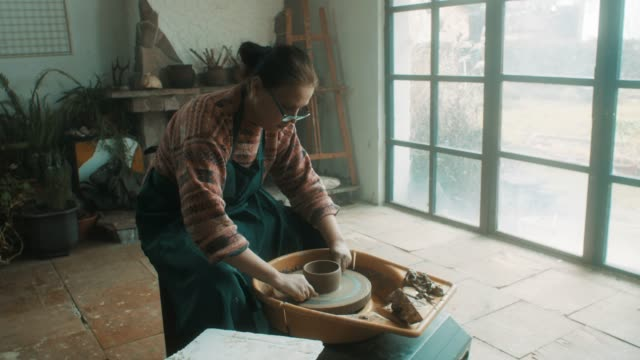 senior woman using pottery wheel at artistic atelier - hobby filmów i materiałów b-roll