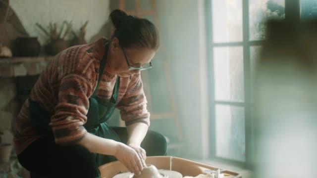 vídeos de stock, filmes e b-roll de mulher sênior usando a roda de oleiro no atelier - cerâmica artesanato