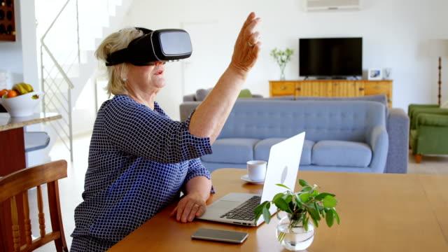 senior woman using virtual reality headset at home 4k - 60 69 anni video stock e b–roll
