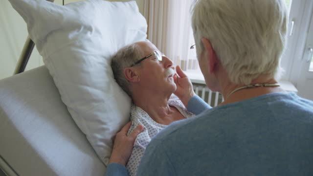 Senior woman visiting sick husband in hospital ward