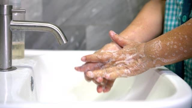 vídeos de stock, filmes e b-roll de idosa lava a mão para prevenção da nova doença de coronavírus 2019. - washing hands