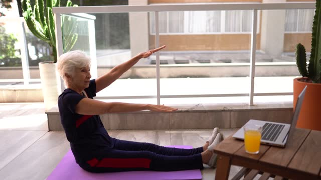 Senior woman watching exercise class and stretching at home video