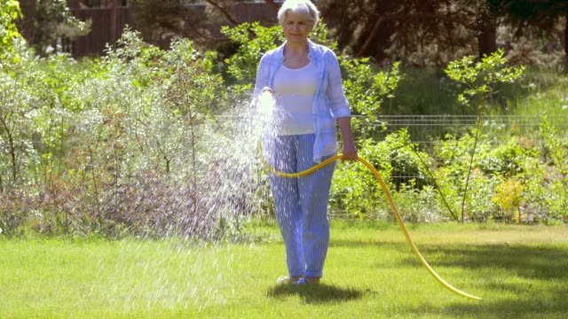 senior woman watering lawn by hose at garden gardening and people concept - happy senior woman watering lawn by garden hose at summer watering stock videos & royalty-free footage