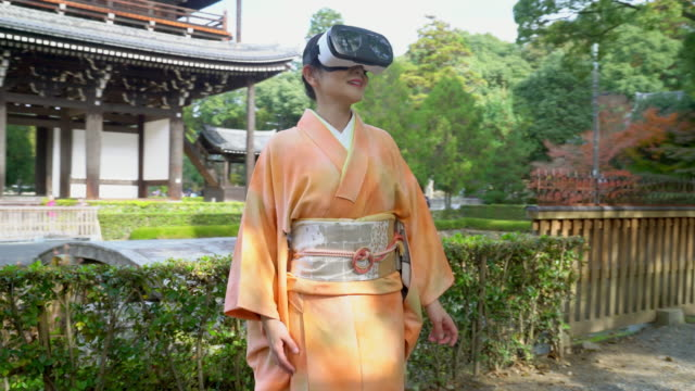 Senior woman wearing a Kimono using a virtual reality headset video