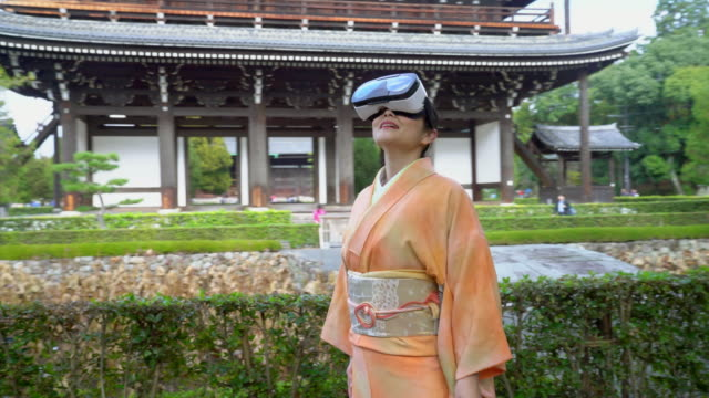 vídeos de stock e filmes b-roll de senior woman wearing a kimono using a virtual reality headset - cidade de quioto