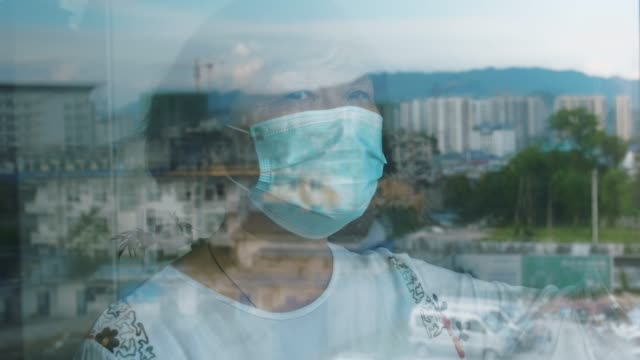 Senior woman wearing a mask and looking through the window
