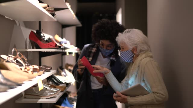 Senior woman wearing face mask being helped by a saleswoman while shopping for shoes in a thrift store