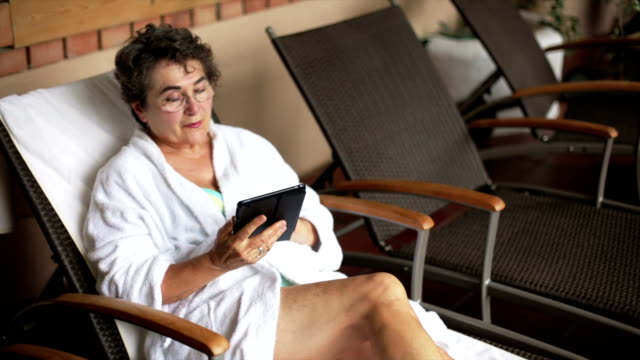 Senior woman web surf on electronic tablet video