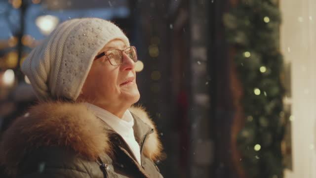 en senior kvinna fönstershoppa på julen när det snöar - cold street bildbanksvideor och videomaterial från bakom kulisserna