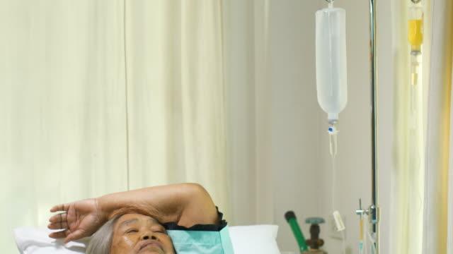 Mujer Senior con un goteo de IV recupera en una cama del hospital sufre de dolor e insomnio - vídeo