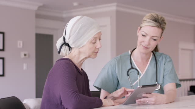 Senior Woman With Cancer At Home With Female Nurse An older senior woman is wearing a headscarf and having an in-home medical check up with her female nurse. They are sitting at a kitchen counter. nutritionist stock videos & royalty-free footage