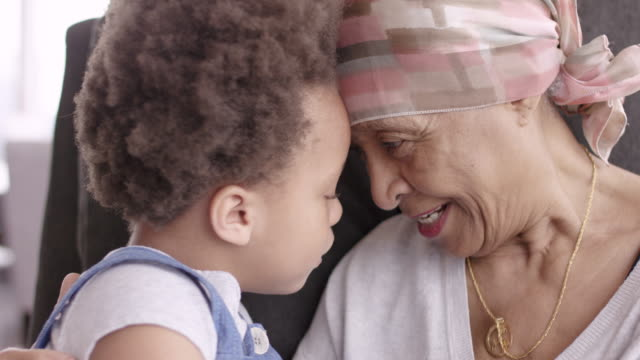 Senior woman with cancer lovingly holds granddaughter A black woman with cancer is wearing a scarf on her head. She is sitting in a lounge chair with her young granddaughter. The two are embracing and their foreheads are touching. They are looking at each other and smiling. The girl is holding her grandmother's necklace. hug stock videos & royalty-free footage