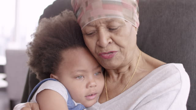 Senior woman with cancer lovingly holds granddaughter A black woman with cancer is wearing a scarf on her head. She is sitting in a lounge chair with her young granddaughter. The two are embracing and they are looking at each other and smiling. cancer illness stock videos & royalty-free footage