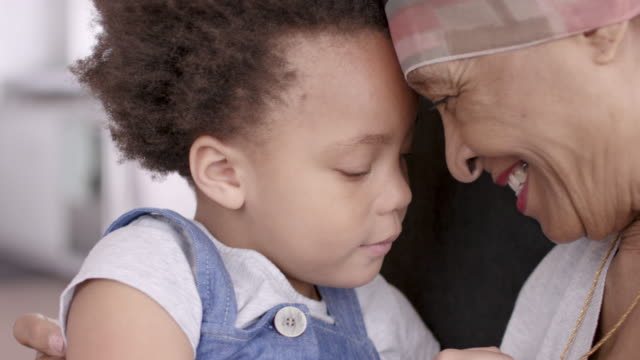 Senior woman with cancer lovingly holds granddaughter A black woman with cancer is wearing a scarf on her head. She is sitting in a lounge chair with her young granddaughter. The two are embracing and their foreheads are touching. They are looking at each other and smiling. The girl is holding her grandmother's necklace. granddaughter stock videos & royalty-free footage