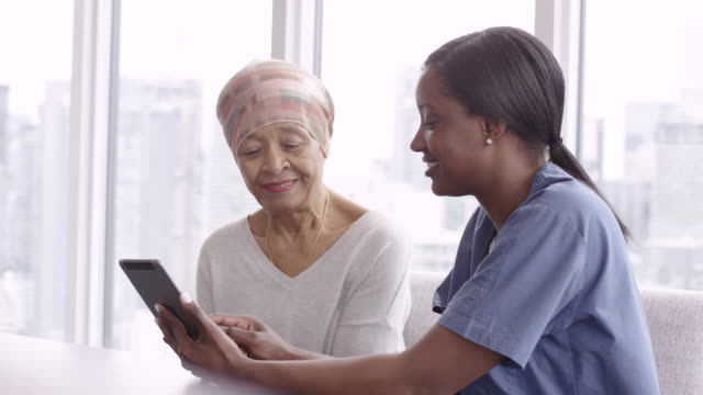 Senior woman with cancer reviews test results with female doctor A woman with cancer is meeting with her doctor. Both individuals are of African descent. The doctor is showing the patient test results on an electronic wireless tablet. They both smile as the doctor gives good news regarding the patient's treatment. cancer patient stock videos & royalty-free footage