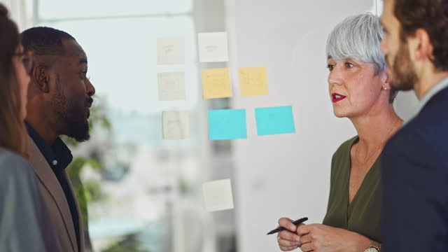 Senior woman with colleagues meeting with sticky notes in office