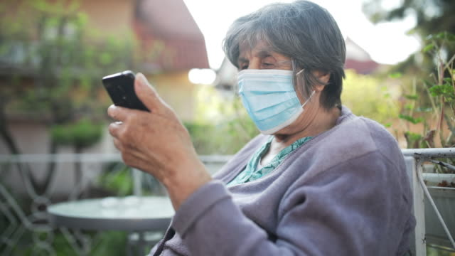 Senior woman with facial mask Senior woman with facial mask using mobile phone in her formal garden,video. face mask videos stock videos & royalty-free footage