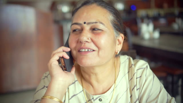 Senior woman with her daughter in restaurant talks on phone.