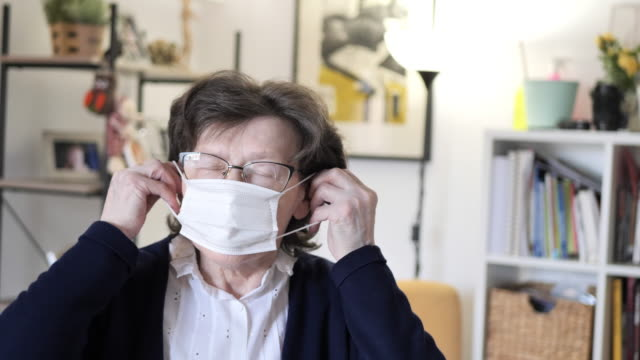 senior woman with hygienic facial mask at home - face mask stock videos & royalty-free footage