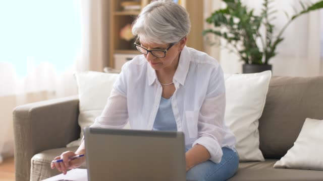 senior woman with laptop and calculator at home - frugal lifestyle stock videos and b-roll footage