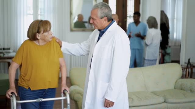 vídeos y material grabado en eventos de stock de mujer mayor con caminante de movilidad hablando con el médico en el asilo de ancianos - geriatría