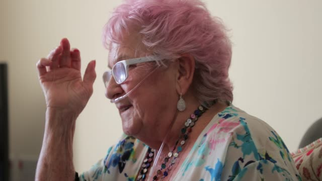 A Senior Woman With Pink Hair A senior woman with pink hair and a nasal cannula to supply oxygen. medical oxygen equipment stock videos & royalty-free footage