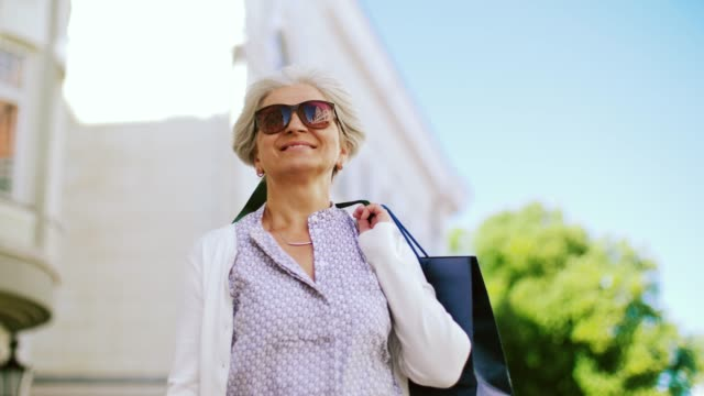 senior woman with shopping bags walking in city - active lifestyle stock videos & royalty-free footage