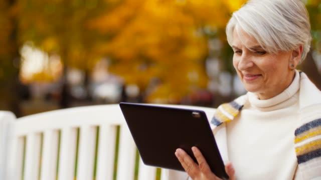 stockvideo's en b-roll-footage met senior vrouw met tablet pc op summer park - een tablet gebruiken