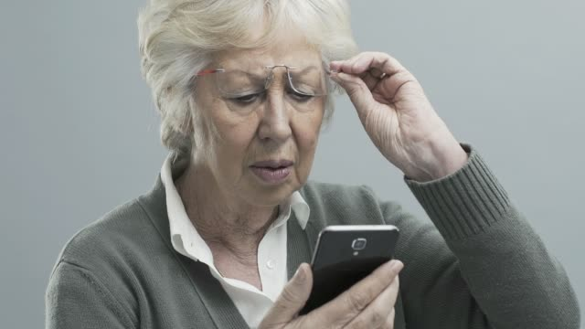 Senior woman with vision problems using a smartphone Senior woman with glasses using a smartphone, she has vision problems and can't focus and read on the digital display eyesight stock videos & royalty-free footage
