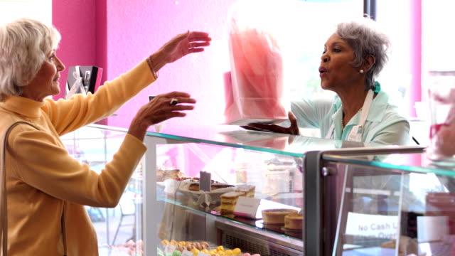 vidéos et rushes de haute femme travaillant dans la pâtisserie, aider le client - relation client