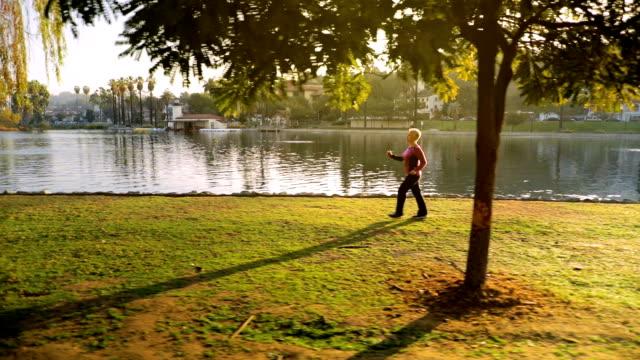 senior kvinna som tränar i parken - naturparksområde bildbanksvideor och videomaterial från bakom kulisserna