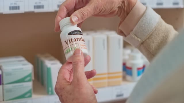 senior woman's hand holding a bottle of d3 vitamins at the drugstore and turning it to check the label - vitamina video stock e b–roll