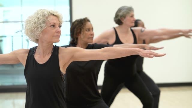 senior women doing yoga - 60 69 anni video stock e b–roll
