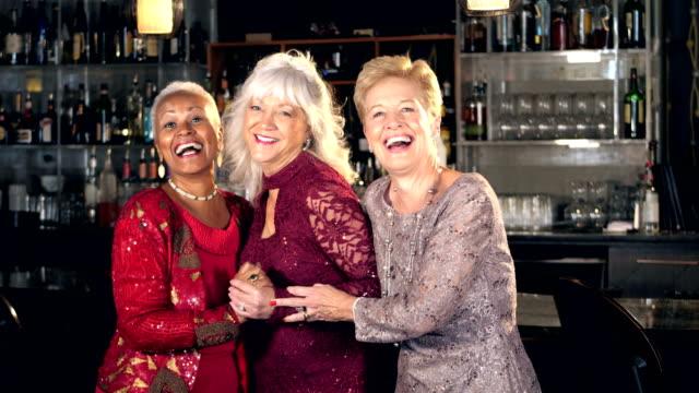 Senior women enjoying night out, standing at the bar video