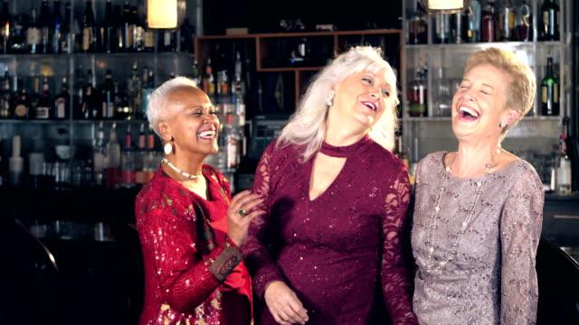 Senior women enjoying night out, talking at bar video