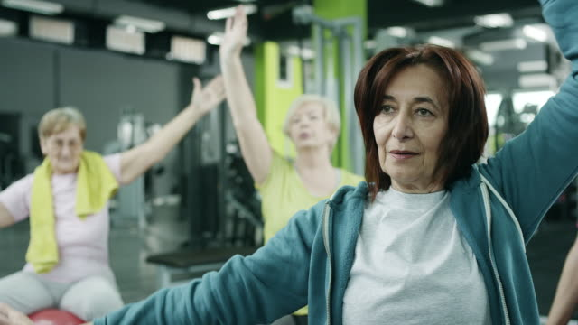 Senior women exercising in gym Class on exercise balls working out in gym medium group of people stock videos & royalty-free footage