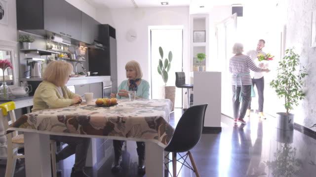 Senior women greeting a young man visiting