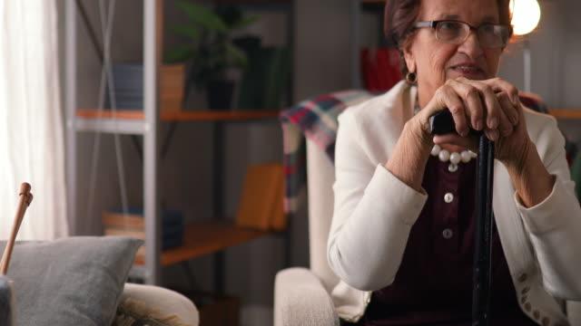 le donne anziane si tiene per mano sul bastone da passeggio - fragilità video stock e b–roll