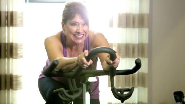 Senior women in gym on exercise bike A senior woman in her 60s smiling as she pedals on an exercise bike at the gym. exercise bike stock videos & royalty-free footage