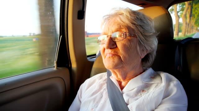 starszy kobiety w samochód o zachodzie słońca - pasażer filmów i materiałów b-roll