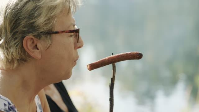 vídeos de stock, filmes e b-roll de mulheres sênior em um piquenique em uma floresta sueca - cachorro quente