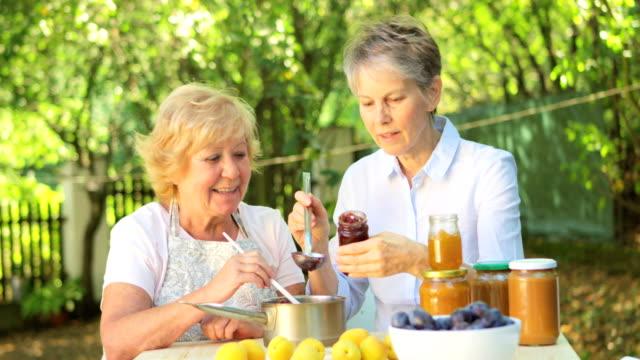 Senior women preparing jam in garden video